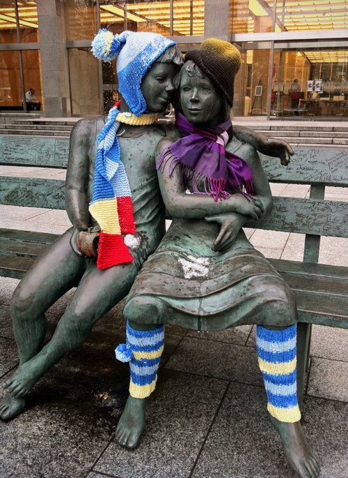 Tejido callejero en estatuas gorros bufandas y calentapiernas en una estatua