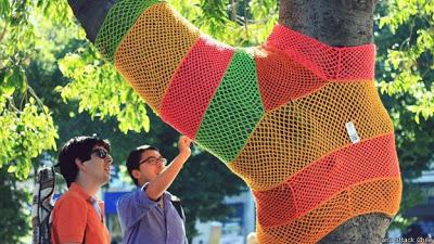 Hombres contemplando un árbol con tejido callejero